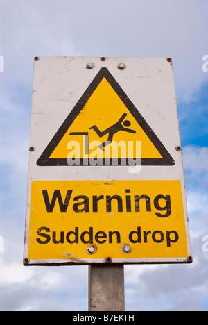 Warning sudden drop sign - Stock Photo