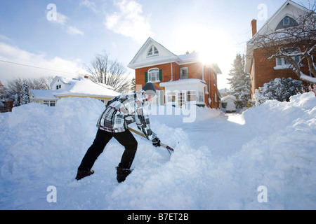 North America Canada Ontario  boy clearing snow in front of house with shovel - Stock Photo