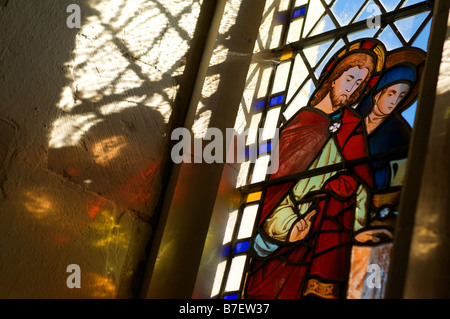 Sunlight pours through an English church stained glass window depicting Jesus Christ - Stock Photo