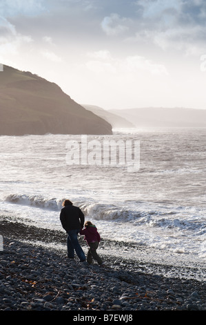 Mother and child walking on the pebble beach at Aberaeron Ceredigion Wales UK on a windy winter afternoon - Stock Photo