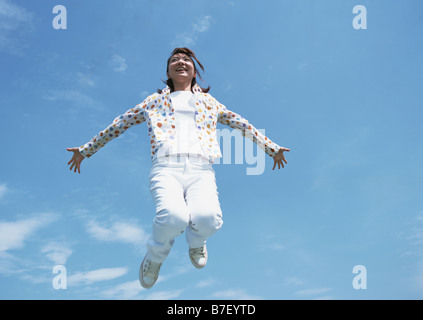 Young woman jumping up in field - Stock Photo