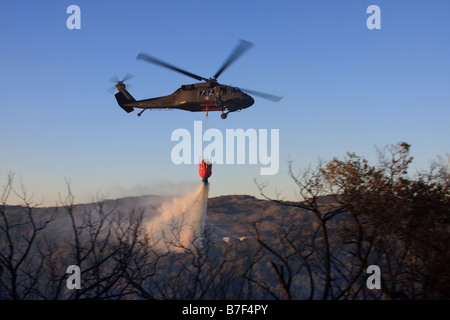 Sikorsky UH-60 Black Hawk helicopter dumping water on a fire. Stock Photo