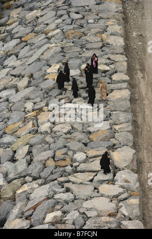Aerial view of eight women in burqas on the rocks by the sea Buyukcekmece Istanbul Turkey - Stock Photo