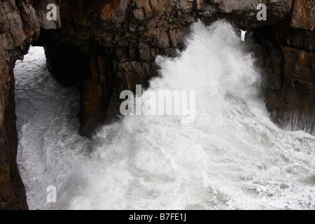Powerful white waves crashing against rocky cliffs, Pembrokeshire Coast, Wales, UK - Stock Photo