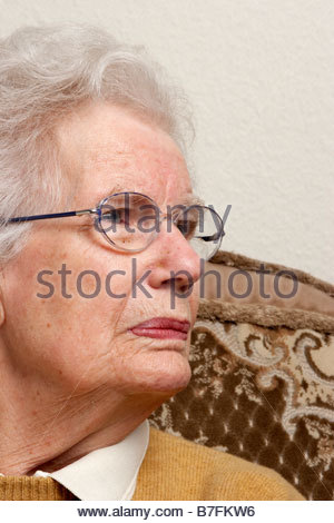 A profile of an old woman sitting in a chair. - Stock Photo