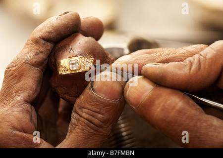 Goldsmith working on an unfinished 22 carat gold ring with his hard working hands Half of the Diamonds already embedded - Stock Photo