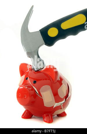 RED  PIGGYBANK BROKEN BY A HAMMER HELD TOGETHER WITH PLASTERS. - Stock Photo