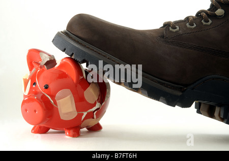 RED  PIGGYBANK BROKEN BY MANS BOOT HELD TOGETHER WITH PLASTERS. - Stock Photo