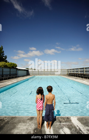 Two children at a swimming pool - Stock Photo