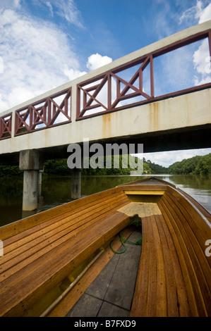 Boat going under bridge on tour of Brunei river and Kampung Ayer water village in Bandar Seri Begawan, Brunei - Stock Photo