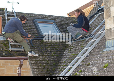 Installing solar thermal evacuated tubes on tiled roof Cotswolds UK - Stock Photo
