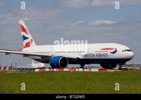 British Airways Boeing 777-236/ER and another commercial airplane taking off in the background at London Heathrow - Stock Photo