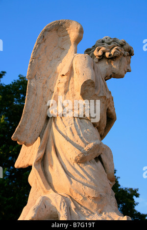 Statue of an angel kneeling humbly before Jesus Christ outside the medieval cathedral of Avignon, France - Stock Photo