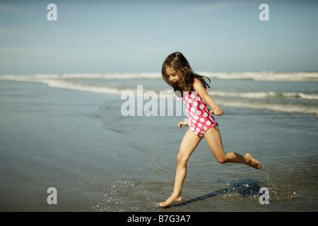 Himatangi beach New Zealand, five year old girl plays in sea - Stock Photo