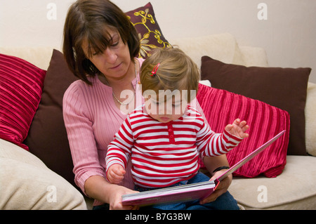 Mother teaching child to read reading together Stock Photo