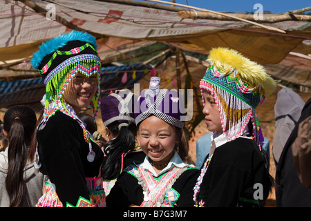 Three young Hmong girls, wearing traditional dress, pose for a picture at a rural Hmong New Year ceremony.