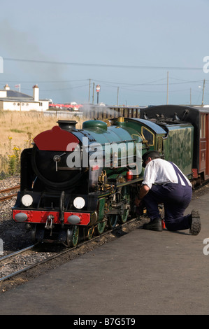 A man working on a miniature steam train - Stock Photo