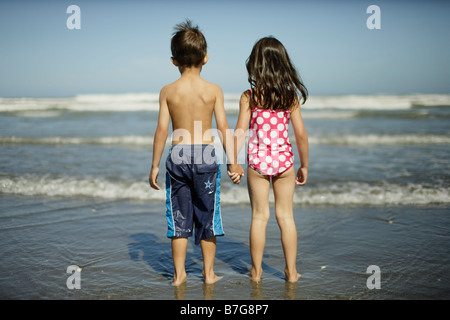 Himatangi beach New Zealand. Girl aged five and boy aged six look out to sea. - Stock Photo
