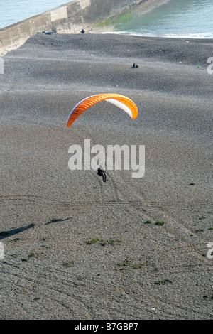 Paraglider Landing on Newhaven Beach from Castle Hill Chalk Cliffs, Newhaven, East Sussex, UK. - Stock Photo