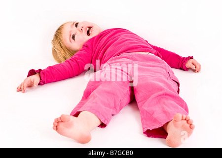 Young female having a temper tantrum on the floor - Stock Photo