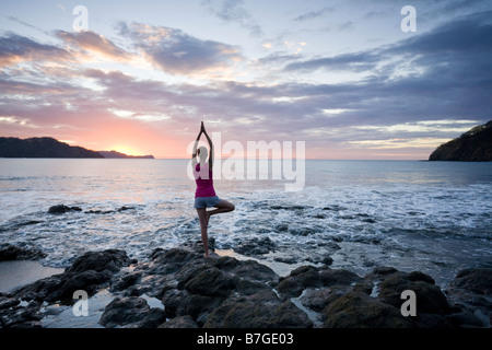 Young woman practicing yoga at sunset in front of ocean surf at Playas del Coco, Guanacaste, Costa Rica. - Stock Photo