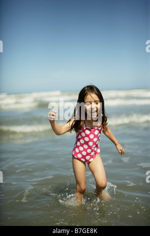 Five year old girl plays in shallow water at Himatangi beach, New Zealand - Stock Photo