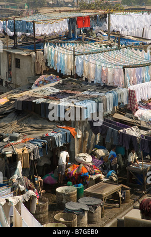 Clothes drying on full clothes lines and Men washing clothes at  Mahalaxmi Dhobi Ghat the worlds' largest open air - Stock Photo