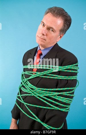 A business man restrained with a colorful rope with a discouraged look on his face - Stock Photo
