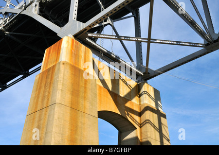 Looking up from under a bridge showing the concrete support steel girders and blue sky - Stock Photo