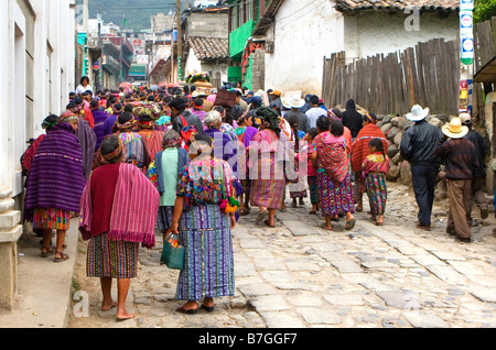 procession of Guatemalan Indians in traditional dress walk through the streets towards the cemetery in Zunil Guatemala - Stock Photo