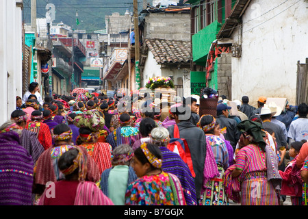A procession of Guatemalan Indians in traditional dress walk through the streets towards the cemetery in Zunil, - Stock Photo