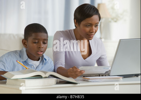 African boy doing homework next mother on computer - Stock Photo