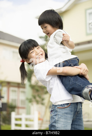 Sister lifting up younger brother - Stock Photo