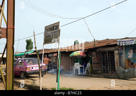A number of people stand in a street in Epe, Nigeria, whilst another man sits and does his paperwork - Stock Photo