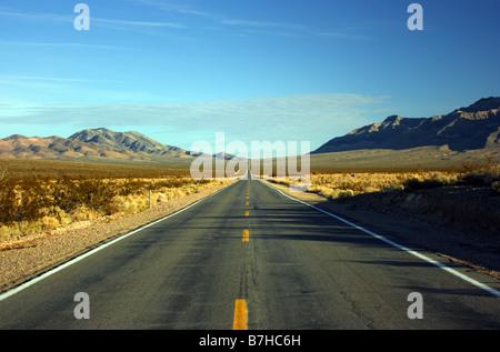 Desert road stretching straight through desert Death Valley California, USA - Stock Photo
