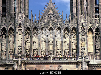 Tourists on balcony below the Gallery of the Kings on west facade of Cathedral Notre Dame Reims France - Stock Photo