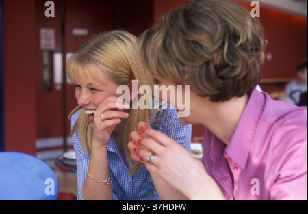 2 young women chatting and laughing together in a restaurant - Stock Photo