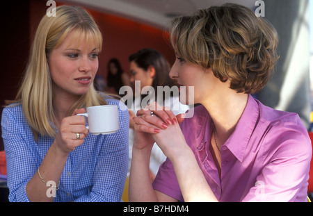 2 women talking seriously over a cup of coffee in a restaurant - Stock Photo