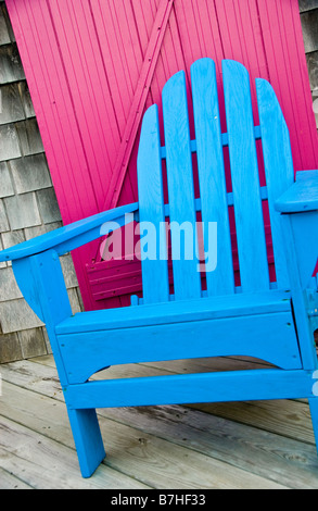A bright blue lounge beach chair made of wood, on a porch with a hot pink or magenta door, in the summer. - Stock Photo