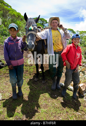 Father and sons posing with cell phones in the countryside near San Nicolas, Western Highlands, Guatemala - Stock Photo