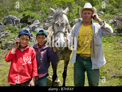 Father and sons posing with cell phones in the countryside near San Nicolas Western Highlands Guatemala - Stock Photo