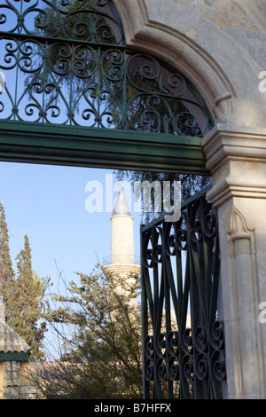 View through Hala Sultan Tekkesi mosque entrance gate near Larnaca, Cyprus on yellow stone minaret. - Stock Photo