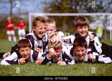 Children. Sport. Group of happy boys celebrating victory at end of Soccer game. - Stock Photo
