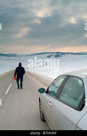 Man Starts the Long Walk Along an Isolated Country Road in Winter to Find Fuel for His Broken Down Car - Stock Photo
