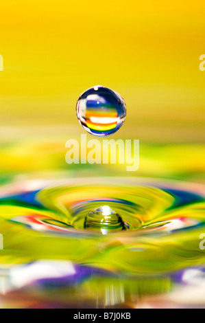 Rainbow coloured water drop and ripple - Stock Photo