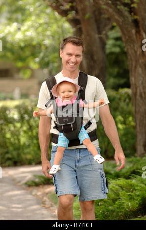 Man walking down street carrying baby in snuggly, Regina, Saskatchewan - Stock Photo