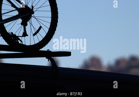 Mountain bike silhouette on the roof of a car in Arches National Park Utah, - Stock Photo