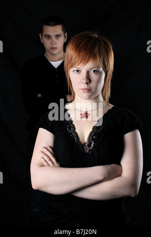 Girl looking annoyed or angry or threateningly at camera with arms folded, boyfriend in the background.  Ginger - Stock Photo