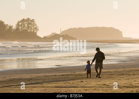 Father &  daughter walk along beach, Chesterman Beach near Tofino, Vancouver Island, British Columbia, Canada - Stock Photo