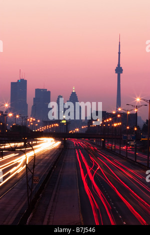 View of Toronto skyline from above Queen Elizabeth Way highway during start of rush hour traffic, Toronto, Ontario, - Stock Photo